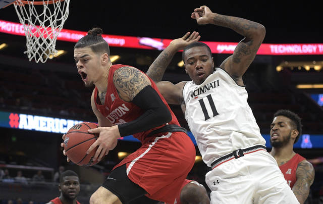 FILE - In this March 11, 2018, file photo, Houston guard Rob Gray, front left, grabs a rebound in front of Cincinnati forward Gary Clark (11) during the first half of an NCAA college basketball championship game at the American Athletic Conference tournament, in Orlando, Fla. America's gambling industry predicts $10 billion will be bet on the March Madness college basketball tournament — nearly all of it illegally or off-the-books. That's one of the reasons the American Gaming Association favors the full legalization and regulation of sports betting in the United States. (AP Photo/Phelan M. Ebenhack, File)