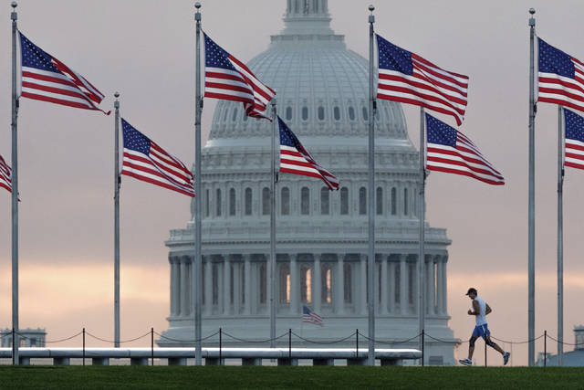 FILE - In this Sept. 27, 2017, file photo, a early morning runner crosses in front of the U.S. Capitol as he passes the flags circling the Washington Monument in Washington. With passage of an enormous budget bill, Congress has all but wrapped up its legislating for the year _ in March. Now lawmakers have to run on what they've got: a tax cut bill, big spending increases and no fixes to immigration. (AP Photo/J. David Ake, File)
