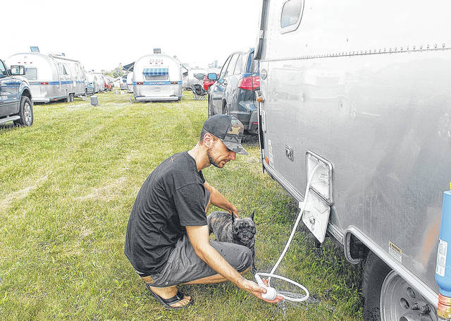 In this 2013 file photo, Steve Etlinger, of Montreal, Canada, prepares to give his French bulldog Abby a quick shower to keep her cool at Alumapalooza Four held at Airstream, Inc in Jackson Center. The festival is for people who love Airstream travel trailers.