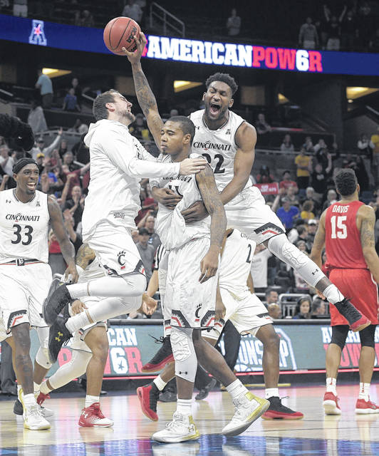 Cincinnati forward Gary Clark, center, is congratulated by forward Jackson Bart, left, and forward Eliel Nsoseme, right, after a 56-55 win over Houston during the American Athletic Conference tournament championship game on Sunday.