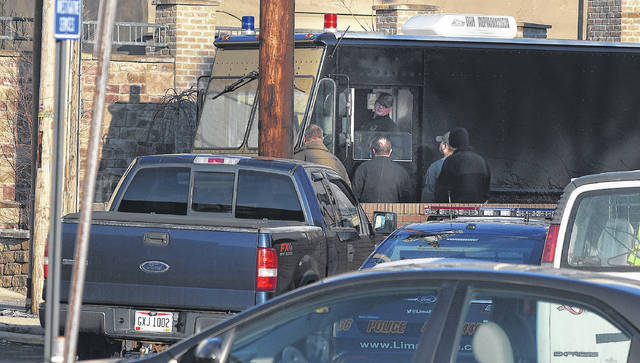 Members of the bomb squad arrive to check a suspicious package behind the municipal building early Thursday morning.