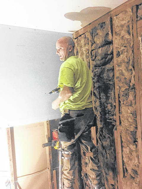 Jeb Halker hangs drywall in a home damaged by Hurricane Harvey in Houston, Texas.