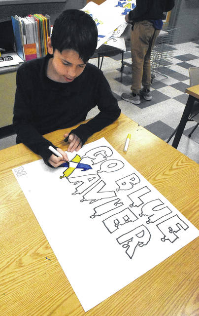 Thomas Burnham, 13, a seventh-grader at Lima West Middle School, draws a poster in art class for Lima native Xavier Simpson, who plays for the University of Michigan.