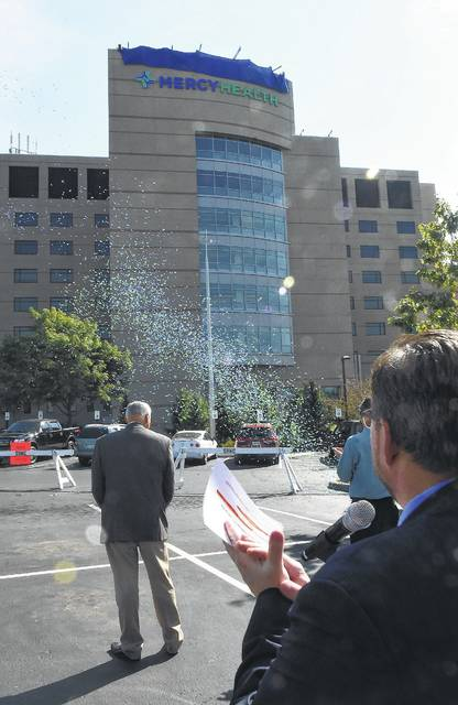 Mercy Health-St. Rita's President Dale Gisi, right, applauds during the unveiling of a new medical center sign in September.
