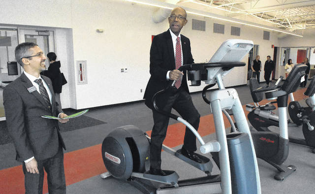 OSU President Michael Drake tries out an elliptical machine in the new Perry Webb Student Life Building during a tour on Friday afternoon. The the left is OSU/Lima Associate Dean, F'abio Leite.