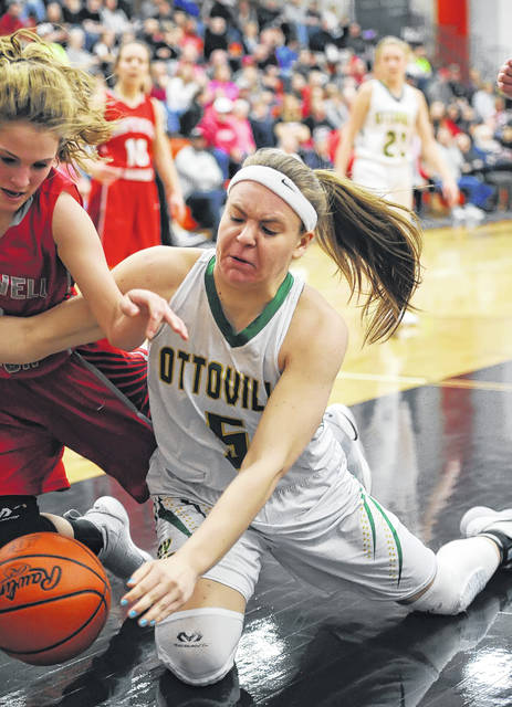 Ottoville's Brynlee Hanneman, left, goes to the floor for a loose along with Hopewell-Loudon's Olivia Zender during a Thursday night Division IV regional semifinal at the Elida Fieldhouse. See more regional photos at LimaScores.com.