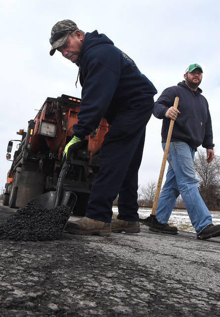 Mike Fox, left and Brandon Barnett, employees with Lima Street Department, fill potholes with hot asphalt along the 800 block of Delphos Ave on Tuesday. Fox and Barnett will fill over 20 potholes a day, weather permitting.  Craig J. Orosz | The Lima News