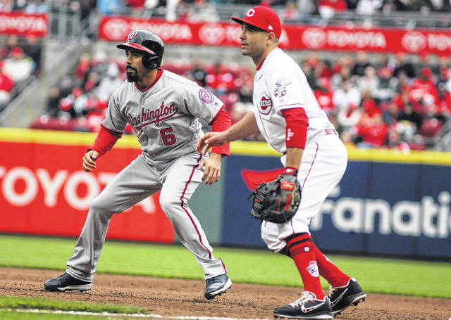 Reds first baseman Joey Votto holds Washington's Anthony Rendon close to the bag during Friday's game at Cincinnati's Great American Ball Park.