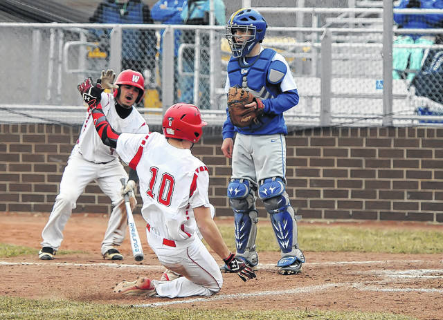 Wapakoneta's Brady Erb safely slides across home plate to score a run against Delphos St. John's during Monday's game at Wapakoenta High School.
