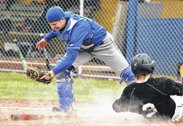 Minster's Alex Lehmkuhl slides safely home under the tag of St. Marys' catcher Trey Fisher's tag during Saturday's doubleheader at St. Marys.
