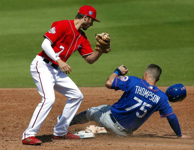 New York Mets' David Thompson (75) steals second base before Washington Nationals shortstop Trea Turner (7) can make the tag during the third inning of a spring training baseball game Thursday in West Palm Beach, Fla. (AP Photo/John Bazemore)