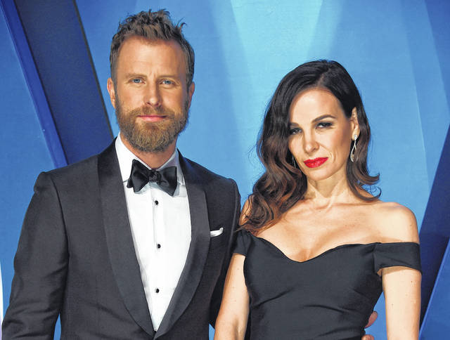 """Dierks Bentley, left, and his wife Cassidy Black arrive at the 51st annual CMA Awards in Nashville, Tenn., in November. Bentley hopes his new single reminds people that he's not always singing about being drunk on a plane, or being a beach bum looking for a rebound. Bentley will perform his new song, """"Woman, Amen,"""" at the Academy of Country Music Awards in Las Vegas on April 15."""