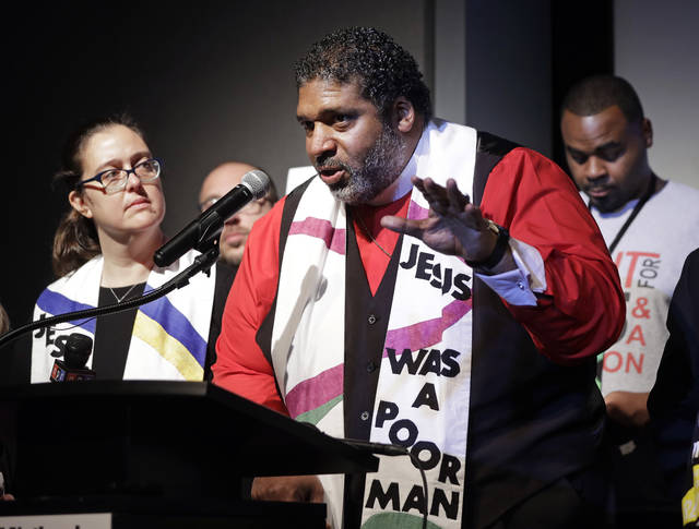 """The Rev. Dr. William J. Barber II, center, and Rev. Dr. Liz Theoharis, left, co-chairs of the Poor People's Campaign, speak at the National Civil Rights Museum Tuesday, April 3, 2018, in Memphis, Tenn. They announced the campaign is preparing for 40 days of non-violent """"direct action"""" in about 30 states that will climax with a rally in Washington this June. The organization is the rekindling of the campaign to help poor people that the Rev. Martin Luther King Jr. was working on when he was killed April 4, 1968, in Memphis. (AP Photo/Mark Humphrey)"""