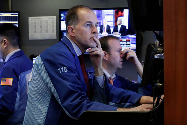 Trader Mark Puetzer works in a booth on the floor of the New York Stock Exchange, Wednesday, April 4, 2018. Stocks are opening sharply lower on Wall Street as an escalating trade dispute between the U.S. and China poses a threat to global economic growth and corporate profits. (AP Photo/Richard Drew)