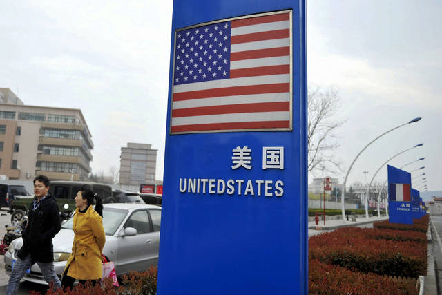 """In this Thursday, April 5, 2018 photo, a couple walk by an American flag signboard on display outside a supermarket selling imported groceries at the Qingdao bonded zone in east China's Shandong province. China is vowing to """"counterattack with great strength"""" if President Donald Trump raises tariffs on an additional $100 billion in Chinese goods. Financial markets tumbled after Trump asked his U.S. trade representative to consider more tariffs. This followed Beijing's announcement that it would increase duties on U.S. soybeans, aircraft and other items. (Chinatopix via AP)"""