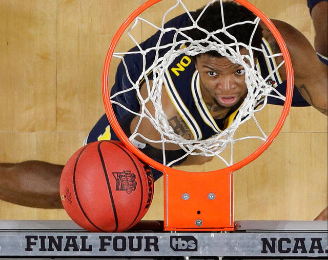 Michigan's Xavier Simpson, a Lima Senior graduate, looks as the ball gets stuck between the basket and the backboard during Monday night's national championship game against Villanova in San Antonio.