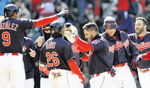 Yan Gomes, center, of the Cleveland Indians, is congratulated by teammates after hitting a two-run home run off Kansas City Royals relief pitcher Brandon Maurer in the ninth inning to give the Indians a 3-1 win on Sunday.