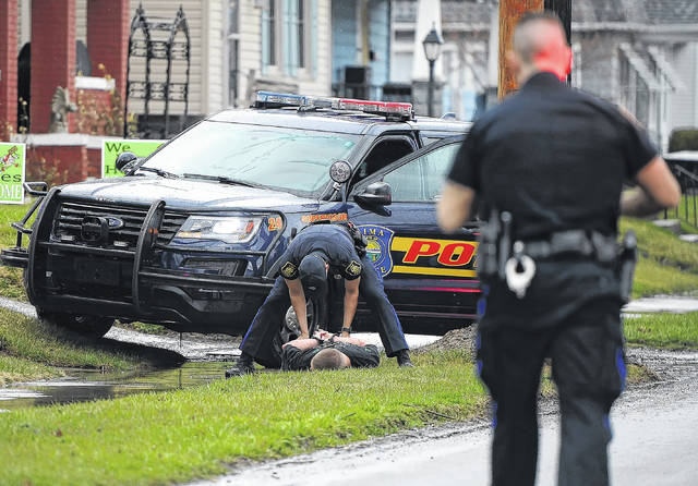 An Lima Police officer handcuffs Dalton Crowe, 26, an alleged stabbing suspect on North Metcalf Street on Tuesday evening. The incident is under investigation.