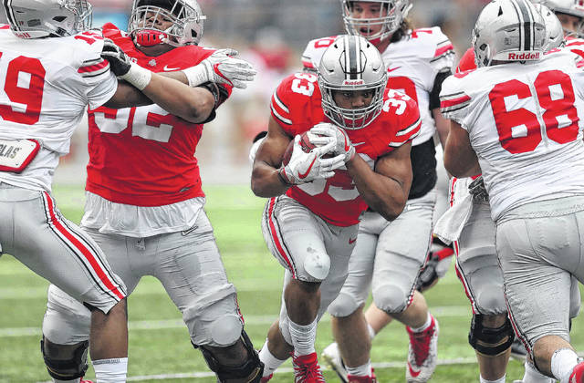 The Scarlet team's Master Teague bursts through the line during Saturday's Ohio State spring game at Ohio Stadium in Columbus.
