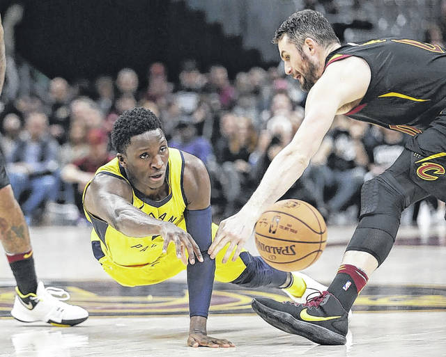 Indiana Pacers guard Victor Oladipo, left, passes against Cleveland Cavaliers' Kevin Love in the second half of Game 1 of an NBA basketball first-round playoff series on Sunday in Cleveland.
