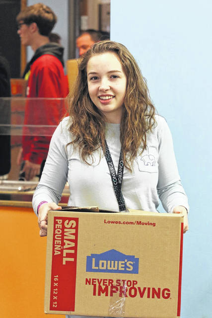 """Savannah Nygren, Sophomore at Van Wert, carries a box of food at 'Our Daily Bread' on Saturday afternoon apart of """"Operation Love Lima"""" which was hosted by the 2018 Converge."""