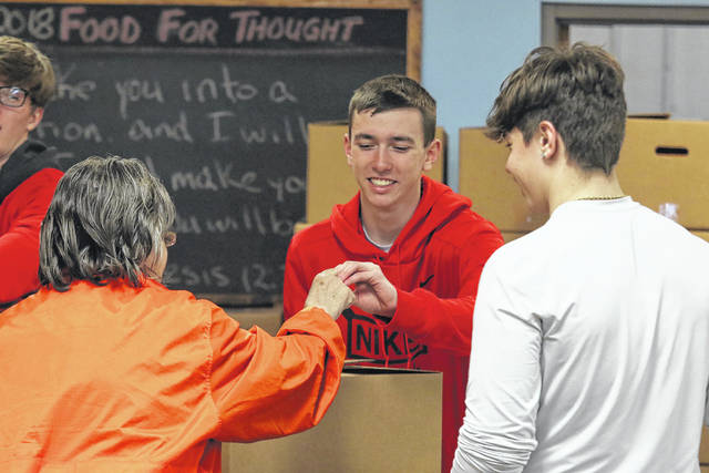 """Keaton Brown, Sophomore at Van Wert, hands out boxes of food that were donated to """"Our Daily Bread"""" by the 2018 Converge for 'Operation Love Lima' on Saturday afternoon."""