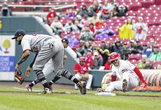 Cincinnati Reds catcher Tucker Barnhart, right, falls to the ground after colliding with St. Louis Cardinals first baseman Jose Martinez, left, during the ninth inning of Sunday's game in Great American Ball Park.