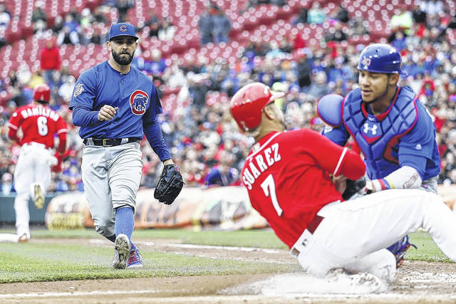 Chicago Cubs starting pitcher Tyler Chatwood, left, watches the play at the plate after fielding a ground ball to catcher Willson Contreras (40) to put out Cincinnati Reds' Eugenio Suarez in the sixth inning of a baseball game, Monday, April 2, 2018, in Cincinnati. (AP Photo/John Minchillo)