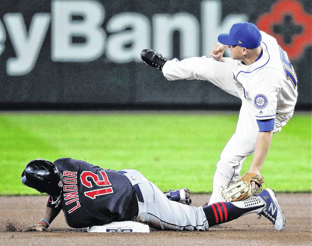 Cleveland Indians' Francisco Lindor (12) safely steals second base as Seattle Mariners third baseman Kyle Seager, right, can't hold on to the ball after a pick-off attempt during the first inning of a baseball game, Sunday, April 1, 2018, in Seattle. (AP Photo/Ted S. Warren)