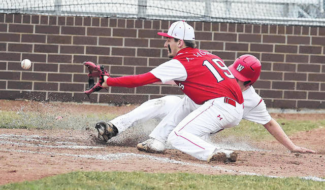 Wapakoneta's Manny Vorhees slides safely into home before Perry's Austin Money receives the throw during Thursday's game at Wapakoenta High School.