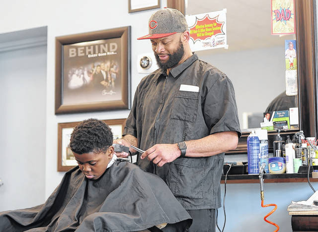 Leandra Johnson cuts the hair of Noah Simpson, 10, on Friday evening.  Johnson is a mentor to kids who come to his shop at Fresh & Faded at 227 S Main Street.  Richard Parrish | The Lima News