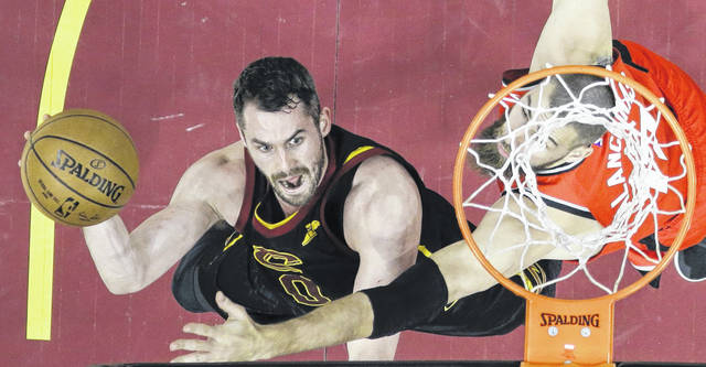 The Cavaliers' Kevin Love puts up a shot against Toronto's Jonas Valanciunas during Monday night's NBA playoff game in Cleveland. Love finished with 23 points as the Cavs closed out the series 4-0 to reach the Eastern Conference finals.