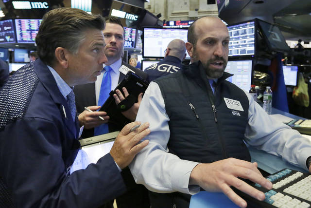 Specialist James Denaro, right, works with traders on the floor of the New York Stock Exchange, Wednesday, May 2, 2018. Stocks are opening moderately lower as Wall Street reacts to another big round of company earnings. (AP Photo/Richard Drew)