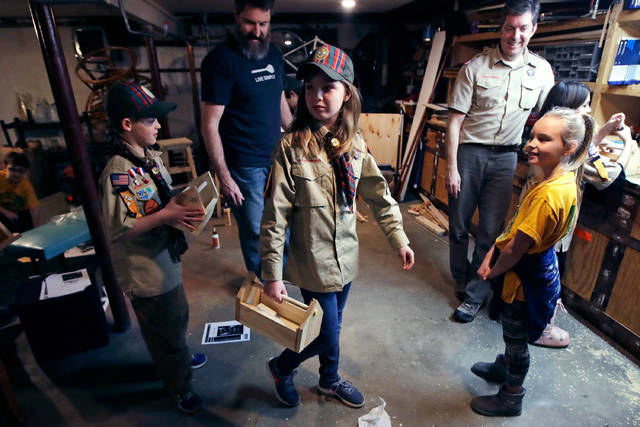 """FILE - In this March 1, 2018, file photo, Tatum Weir, center, carries a tool box she built as her twin brother Ian, left, follows after a Cub Scout meeting in Madbury, N.H. Fifteen communities in New Hampshire are part of an """"early adopter"""" program to allow girls to become Cub Scouts and eventually Boy Scouts. For 108 years, the Boy Scouts of America's flagship program for older boys has been known simply as the Boy Scouts. With girls soon entering the ranks, the BSA says that iconic name will change to """"Scouts BSA."""" The change will take effect in February 2019. (AP Photo/Charles Krupa, File)"""