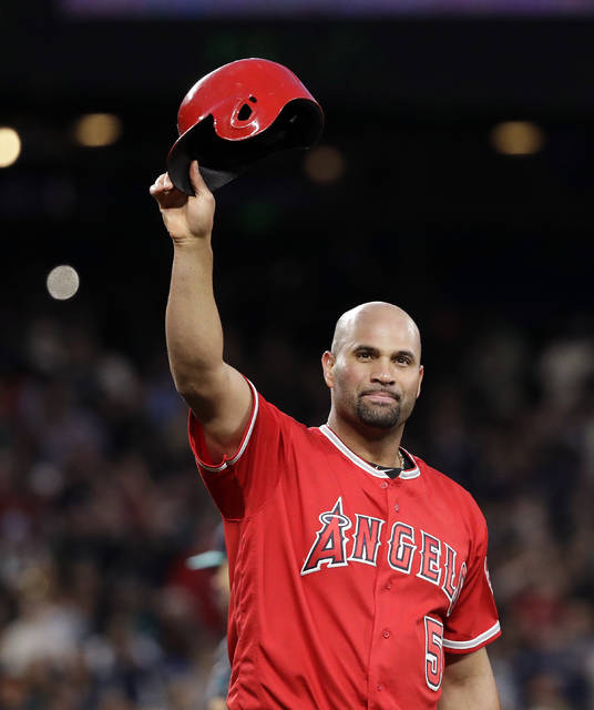 Los Angeles Angels' Albert Pujols waves his helmet to fans after hitting a single against the Seattle Mariners in the fifth inning of a baseball game Friday, May 4, 2018, in Seattle. The hit was his 3,000th of his career. (AP Photo/Elaine Thompson)