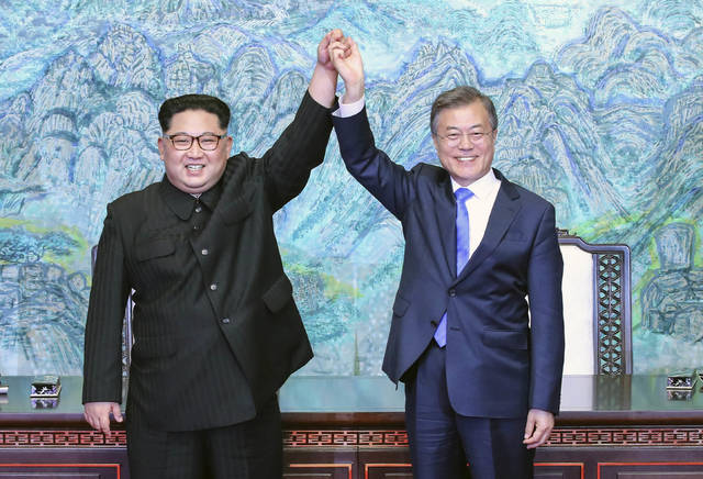 """File-This April 27, 2018, file photo shows North Korean leader Kim Jong Un, left, and South Korean President Moon Jae-in raising their hands after signing a joint statement at the border village of Panmunjom in the Demilitarized Zone, South Korea. North Korea readjusted its time zone to match South Korea's on Saturday and described the change as an early step toward making the longtime rivals """"become one"""" following a landmark summit. North Korean leader Kim Jong Un promised to sync his country's time zone with the South's during his April 27 talks with South Korean President Moon Jae-in. A dispatch from the North's Korean Central News Agency says that promise was fulfilled Saturday by a decree of the nation's Presidium of the Supreme People's Assembly. (Korea Summit Press Pool via AP, File)"""