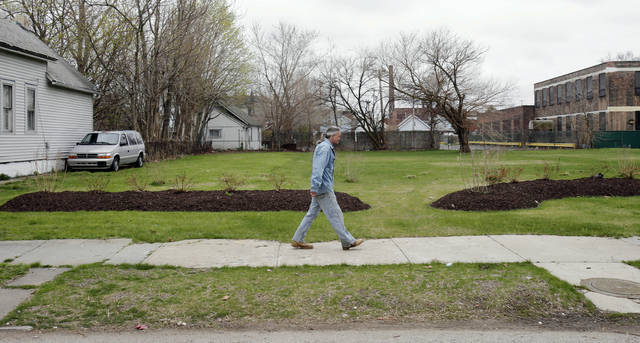FILE - In this April 23, 2014 file photo, a man walks past an empty lot, which once was the home of Ariel Castro in Cleveland. Residents on the street where three women were held captive say they're tired of being eyed by spectators who still visit the site five years after Ariel Castro's house of horrors was demolished. It has been reported that cars and buses continue to crawl past the lot where Castro's home once stood.  (AP Photo/Tony Dejak)