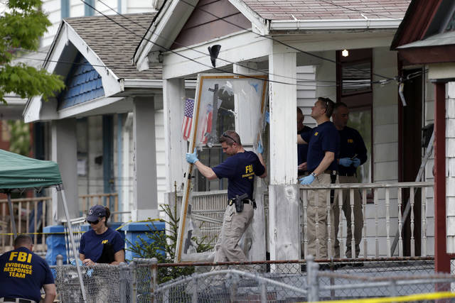 FILE - In this May 7, 2013 file photo, members of the FBI evidence response team carry out the front screen door from the Cleveland home of Ariel Castro, where three women escaped after 10 years of captivity. Residents on the street where three women were held captive say they're tired of being eyed by spectators who still visit the site five years after Ariel Castro's house of horrors was demolished. It has been reported that cars and buses continue to crawl past the lot where Castro's home once stood. (AP Photo/Tony Dejak, File)