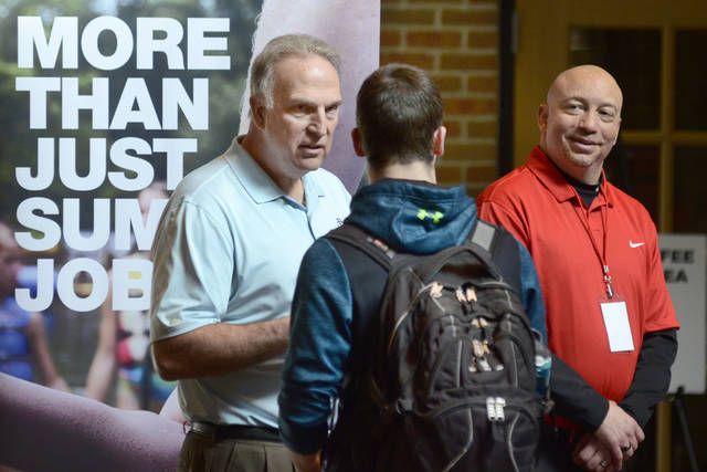 FILE - In this March 14, 2018 file photo, Dan Cieslak, left, a Human Resources representative for the Dunham's Distribution Center, and Warren Whitlow, a training manager, speak to students and other visitors during the Experience Indiana job fair event in the student center at Indiana Wesleyan University in Marion, Ind. U.S. employers advertised 6.6 million open jobs in March, the most on records dating back to December 2000, suggesting businesses want to staff up to meet strong demand. Job openings rose 7.8 percent in March from 6.1 million in February, the Labor Department said Tuesday, May 8.  Yet overall hiring slipped, while quits increased. (Jeff Morehead /The Chronicle-Tribune via AP, File)