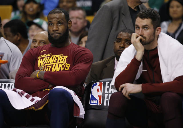 Cleveland Cavaliers forward LeBron James, left, and center Kevin Love, right, watch from the bench during the fourth quarter of Game 1 of the NBA basketball Eastern Conference Finals against the Boston Celtics, Sunday, May 13, 2018, in Boston. (AP Photo/Michael Dwyer)