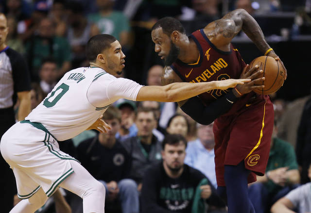 Cleveland Cavaliers forward LeBron James, right, looks to make a move against Boston Celtics forward Jayson Tatum (0) during the second half of Game 1 of the NBA basketball Eastern Conference Finals, Sunday, May 13, 2018, in Boston. (AP Photo/Michael Dwyer)