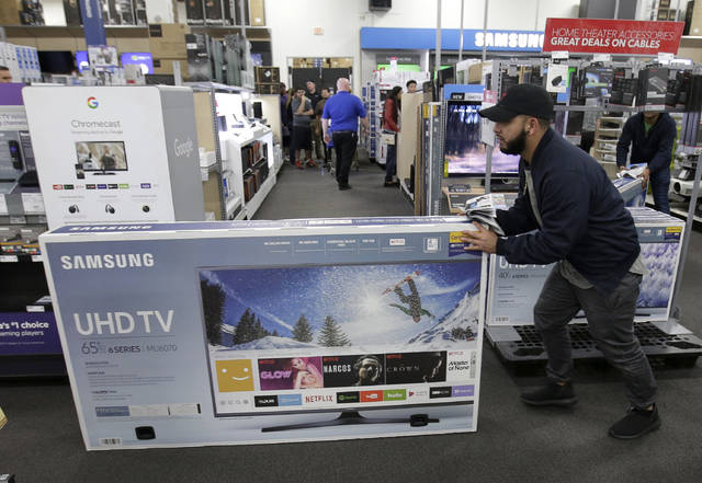 FILE - In this Nov. 23, 2017, file photo, Jesus Reyes pushes a television down an aisle as he shops at a Black Friday sale at a Best Buy store in Overland Park, Kan. On Tuesday, May 15, 2018, the Commerce Department releases U.S. retail sales data for April. (AP Photo/Charlie Riedel, File)