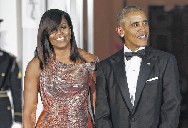 Former President Barack Obama and First Lady Michelle Obama wait to greet Italian Prime Minister Matteo Renzi and his wife Agnese Landini for a State Dinner in October 2016 at the White House in Washington. Netflix says it reached a deal with the two to produce material for the streaming service.