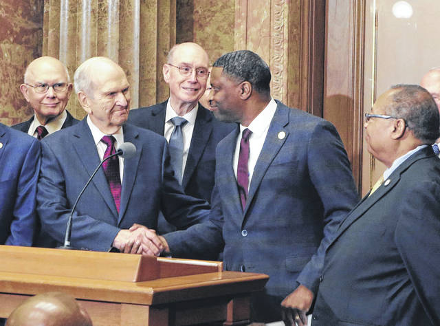 """FILE - In a Thursday, May 17 file photo, Mormon church President Russell M. Nelson shakes hands with Derrick Johnson, president of the NAACP during a news conference, in Salt Lake City. The Mormon church did not issue an apology for a """"history of racism"""" during a news conference this week with NAACP leaders, despite a false news release posted on a website made to look strikingly similar to one used by the church."""