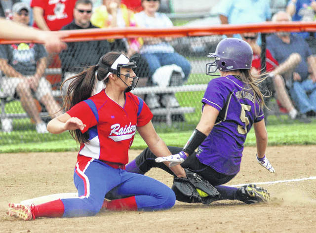 Ada's Nicki Lehsten slides into third base before Wayne Trace's Megan Moore can apply the tag during a Wednesday Division IV district semifinal at Elida.
