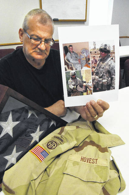 Barney Novest holds a photograph of his son Benjamin with his jacket and flag. Benjamin was an Army Ranger in the Iraq war that suffered from PTSD and took his life in 2016.