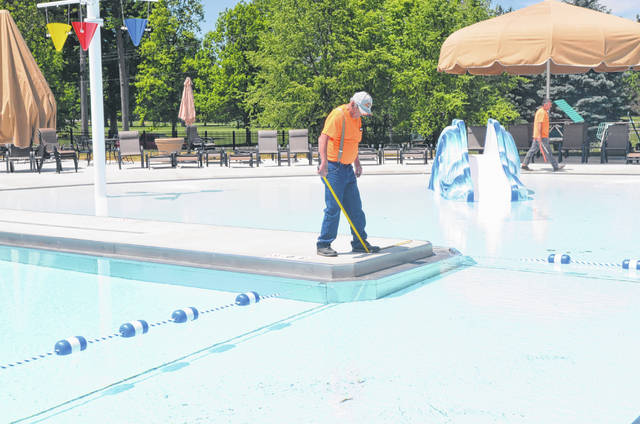 Steve Torax, of Astro Pool Company, works on finishing touches of the newly rennovated pool that will open Saturday at the Shawnee Country Club on 1700 Shawnee Road.