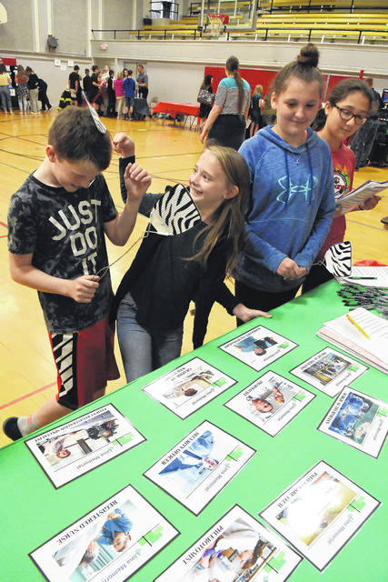 """Toying with flyswatters after playing a game of """"Swat that Career"""" are Tristan Anderson, 12, left, Isabella Moore, 12, after answering questions from Lima Memorial Health System career table at Shawnee Middle School. The school hosted its second annual career fair on Thursday with 26 area professionals volunteering their time to discuss their career fields with sixth through eighth grade students. To the far right watching the game are Trish Dean, 12, and Karina Delgado, 11, all four students are sixth graders."""