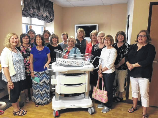 Members of the Guiding Mothers of St. Marys Ohio Child Conservation League are pictured with a Nara bassinette the group donated for the birthing center at Joint Township District Hospital.