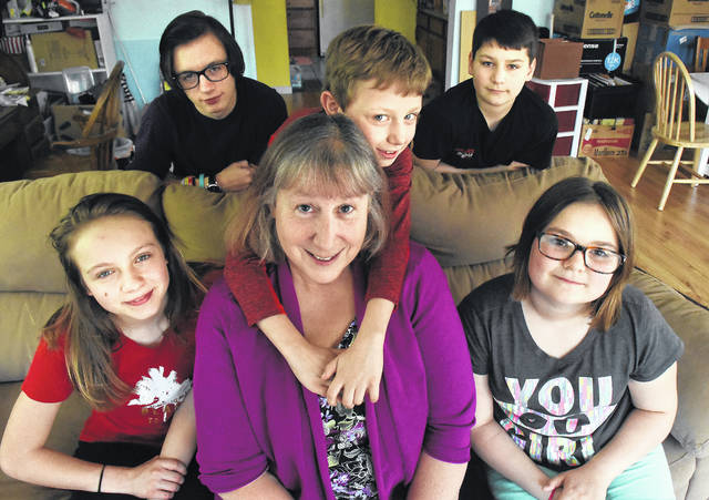 Marge Rowe at home in Allentown with her five adopted children, Nate Hefner, 16, Zeeke Clark, 14, Genesis Hefner, 13, Zayia Clark, 11, and Gideon Hefner, 9, holding Marge.